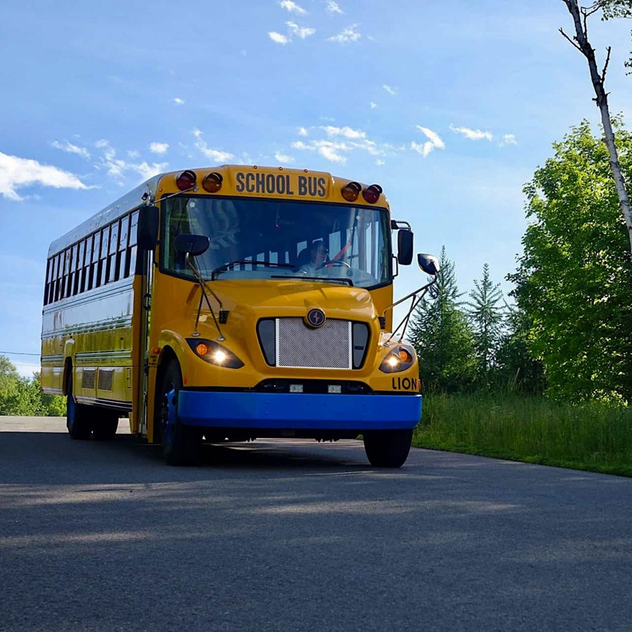 A photo of the MA pilot program shows electric school buses can cut GHG emissions in half project