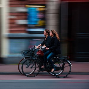 women riding bicycles through a city
